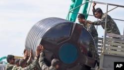 Anggota militer Maladewa mengangkat tangki air ke sebuah kendaraan militer untuk diisi dengan air di Male', 5 Desember 2014.