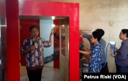 Rektor Institut Teknologi Telkom Surabaya (ITTS), Tri Arif Sardjono, menunjukkan cara kerja tunnel sterilisasi buatan ITTS untuk mencegah penyebaran virus corona (foto Petrus Riski-VOA).jpg