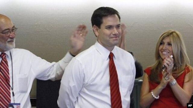 Republican Florida Senator-elect Marco Rubio and his wife Jeanette smile as national TV stations call the race in his favor while watching results in Coral Gables, Florida, 2 Nov. 2010
