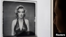 FILE - A visitor looks at the picture 'Marilyn Monroe, Actress, New York City, May 6, 1957' by photographer Richard Avedon (1923-2004).
