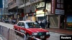 Sebuah taksi melintasi jalanan di pusat perdagangan Causeway Bay, Hong Kong (Foto: dok). Pihak berwenang China menjanjikan perubahan dalam industri taksi pasca pemogokan para supir di sedikitnya tujuh kota utama negara itu.
