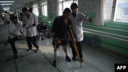FILE - An Afghan doctor, right, assists a survivor of a land mine blast at a hospital run by the International Committee of the Red Cross for war victims and the disabled in Kabul, Feb. 13, 2018. The Taliban announced Oct. 11, 2018, that it would allow the ICRC to fully resume operations in Afghanistan.