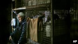 Yeung Ying Biu, 77, duduk dalam tempat tinggalnya, 'kandang' berukuran 1,5 meter persegi di sebuah bangunan kumuh di Hong Kong. (AP/Vincent Yu)