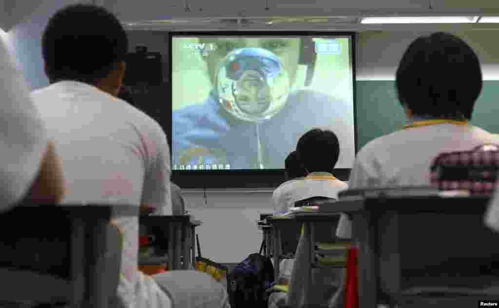 Students watch a live broadcast of a lecture given by astronauts on the Tiangong-1 space module, at a school in Beijing, June 20, 2013.