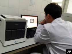 A staffer works at a laptop next to an American-made GeneXpert machine used to diagnose tuberculosis at the National Tuberculosis Reference Laboratory in Pyongyang, North Korea, May 7, 2018. The machines at the lab can't be used because officials can't procure the materials they need to operate them.