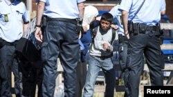 Một cậu bé di dân khóc trong khi tìm cách ngăn mẹ rời tàu để lên xe buýt tại trạm xe lửa Rodby ở miền nam Denmark hôm 9/9/2015.
