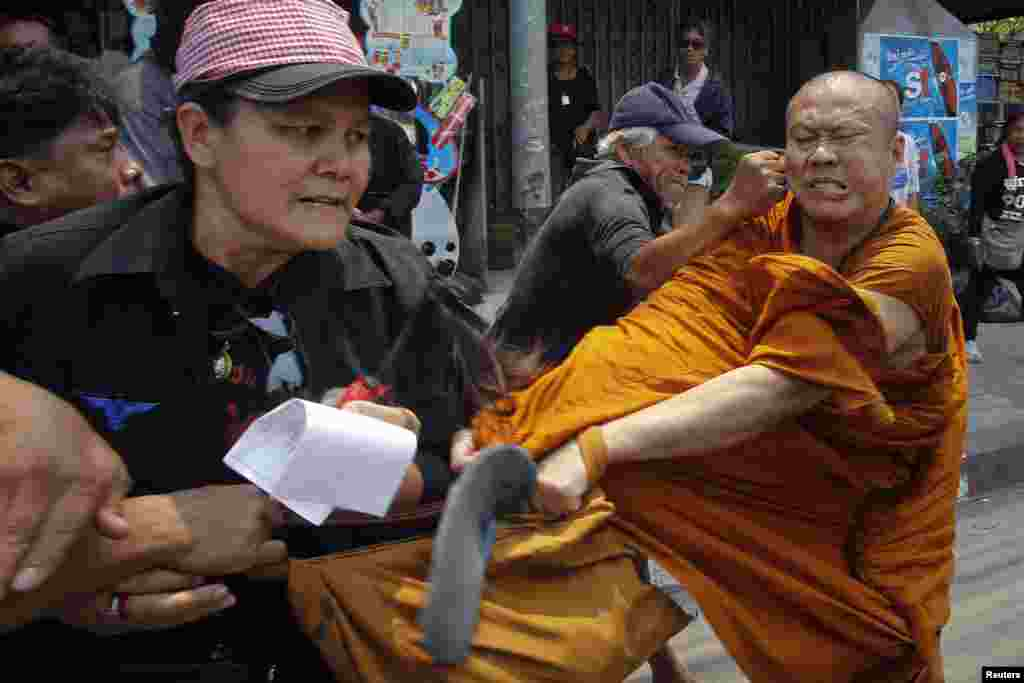 "Members of the pro-government ""red shirt"" movement attack a Buddhist monk outside the National Anti-Corruption Commission office in Nonthaburi province, on the outskirts of Bangkok, Thailand."