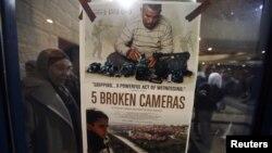 """Poster film dokumenter nominasi Oscar """"5 Broken Cameras"""" dipasang di bioskop di Ramallah, Tepi Barat (28/1). (Reuters/Mohamad Torokman)"""