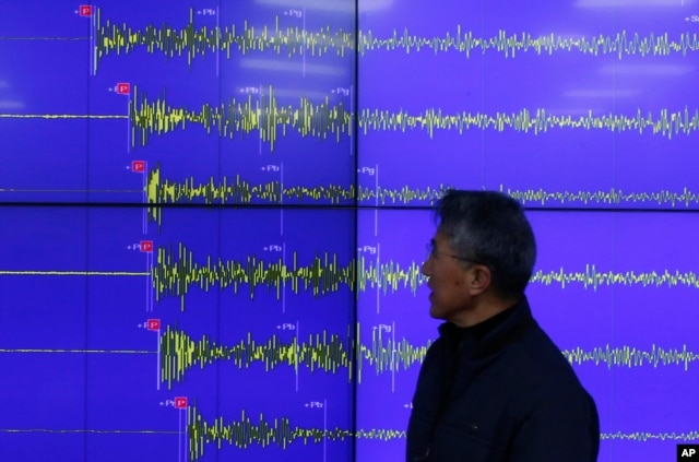 FILE - Yun Won-tae of the Korea Meteorological Administration stands in front of a screen showing seismic waves that were measured in Seoul after North Korea said it had conducted a powerful hydrogen bomb test, Dec. 6, 2015.
