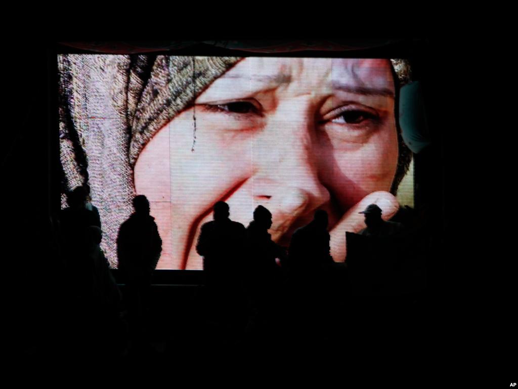 (美联社) 2012年一月二十五号傍晚在开罗解放广场放映的录像显示在与埃及安全部队冲突中丧生的受害人家属