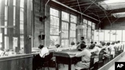 Young women at work in the US Radium factory in Orange, New Jersey in the mid-1920s. Many became ill and died after working with radioactive glow-in-the-dark paint.