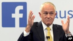 FILE - Australian Prime Minister Malcolm Turnbull raises his hands as he speaks during a leaders debate hosted by Facebook Australia and News.com.au in Sydney, June 17, 2016. The Australian government on July 14, 2017, proposed a new cybersecurity law to force global technology companies such as Facebook and Google to help police by unscrambling encrypted messages sent by suspected extremists and other criminals.