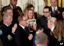 Jeanne Moser, center, of East Kingston, N.H., watches as President Donald Trump reaches out to touch a photo of her son Adam Moser, during a event to declare the opioid crisis a national public health emergency. Adam was 27 when he died from an apparent fentanyl overdose.