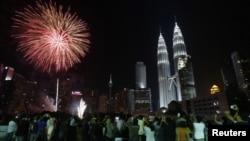 Kembang api berpendar dekat menara kembar Petronas di Kuala Lumpur.