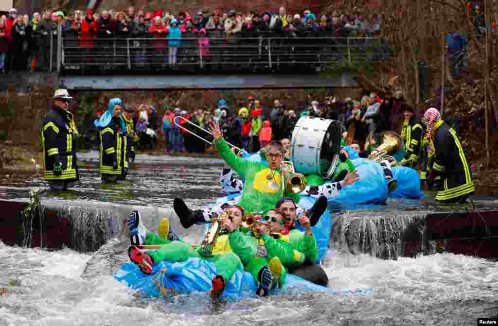 Carnival celebrators with self-made floats ride down the Schiltach stream during the 'Bach na fahre' (race down the stream) raft contest in Schramberg, Germany.