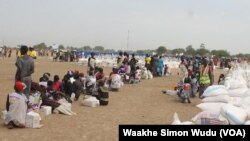 Displaced South Sudanese wait on Saturday, March 21, 2015, in Ganyiel, Unity state for sacks of food provided by the World Food Program (WFP) to be distributed.