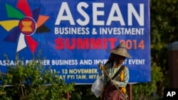 A sweeper cleans a road in the foreground of a billboard promoting Association of Southeast Asian Nations (ASEAN) summit in Naypyitaw, Myanmar, Tuesday, Nov 11, 2014. Myanmar hosts the ASEAN summit and related meetings on Nov. 12 and 13. (AP Photo/Gemunu