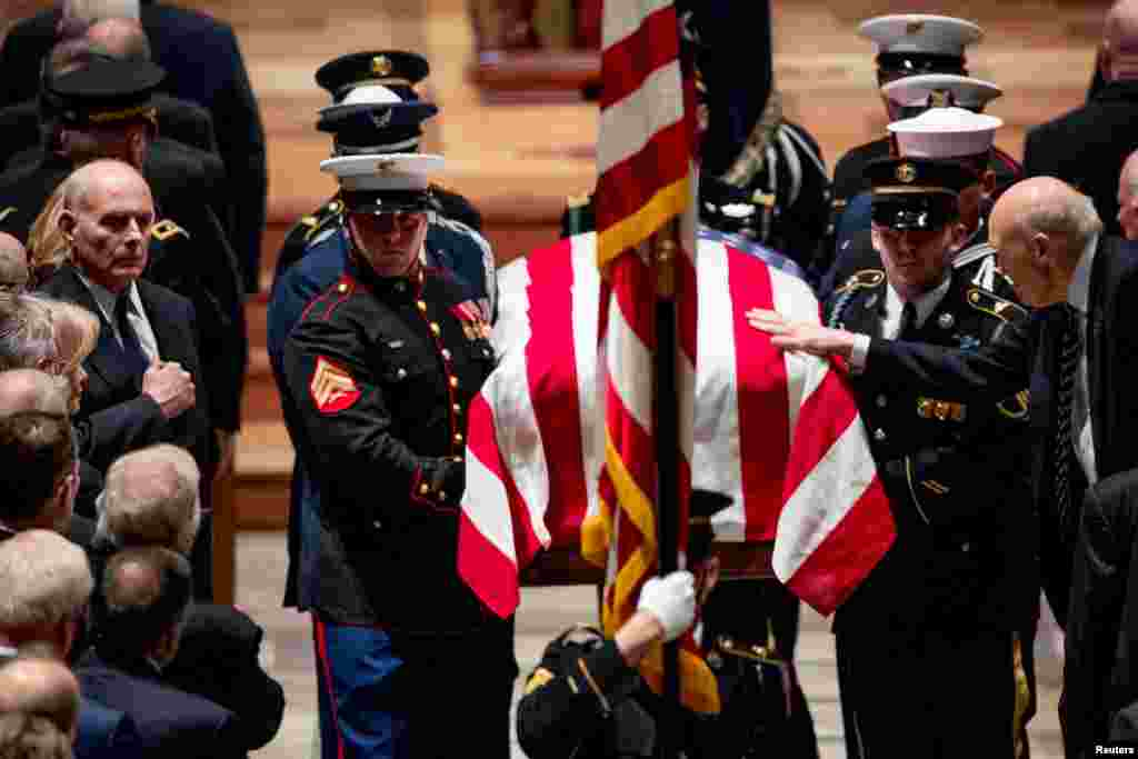 Former Sen. Alan Simpson (R-WY) touches the flag-draped casket of former President George H.W. Bush as it is carried out by a military honor guard during a State Funeral at the National Cathedral in Washington, Dec. 5, 2018.