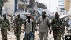 Somali government soldiers patrol a section of Bakara market following the demolition of illegal structures erected next to access roads in Mogadishu, April 30, 2012.