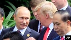Le président russe Vladimir Poutine, à gauche, et le président américain Donald Trump discutent lors de la séance de photos de famille en marge du sommet de la Coopération économique Asie-Pacifique (APEC) à Danang, Vietnam, 11 novembre 2017.