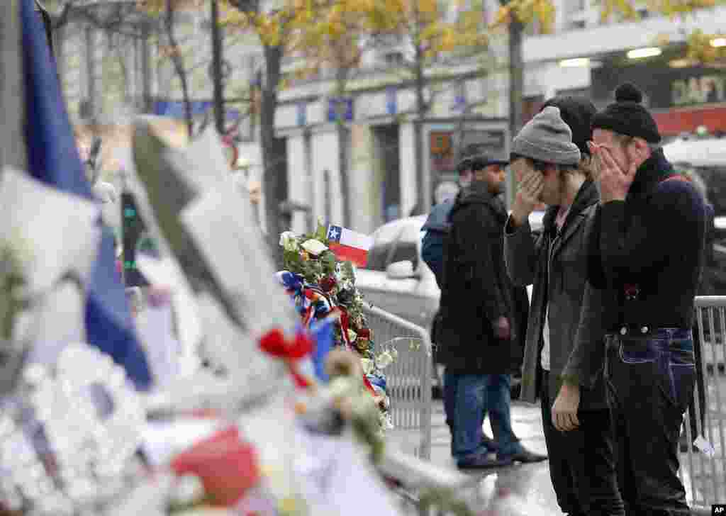 Members of the band Eagles of Death Metal, Jesse Hughes, right, and Julian Dorio pay their respects to victims who died in the Nov. 13 terrorist attack, at the Bataclan concert hall in Paris, France. Members of the California rock band are back at the ravaged Paris theater where they survived a massacre by Islamic extremists.