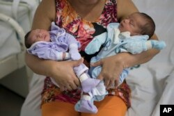 FILE - Severina Raimunda holds her granddaughter Melisa Vitoria, left, who was born with microcephaly and her twin brother, Edison Junior, at the IMIP hospital in Recife, Pernambuco state, Brazil, Feb. 3, 2016.