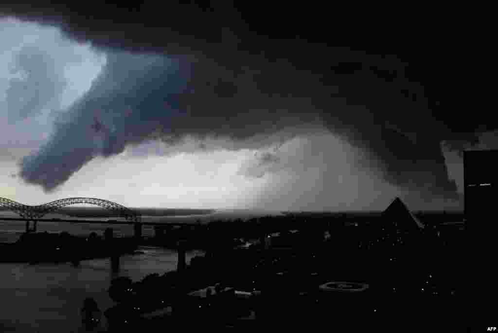 25/5: Nhiều trận bão lớn băng ngang sông Mississippi, gần thành phố Memphis, tiểu bang Tennessee. Vùng trời màu đen được chụp vài phút trước khi gió lốc thổi qua thành phố West Memphis, tiểu bang Arkansas. (AP Photo)