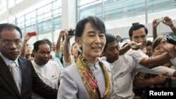 Myanmar's pro-democracy leader Aung San Suu Kyi makes her way through the Yangon International Airport as she leaves for her trip to Europe June 13, 2012.