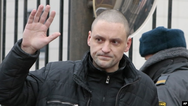 Russian opposition leader Sergei Udaltsov waves to the media before entering the Russian Investigative Committee's office in Moscow, Russia, Friday, Dec. 14, 2012.