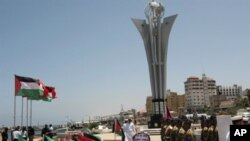 Hamas security men stand near flags from different countries and a monument built to commemorate the first anniversary of the death of nine Turks, who were shot dead last May when Israeli naval commandos seized a Turkish ship that was part of a flotilla t