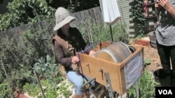 Katherine Jolda sedang mengayuh pedal pemintal benang yang digunakan untuk membuat pakaian dan asesoris lokal yang ramah lingkungan.
