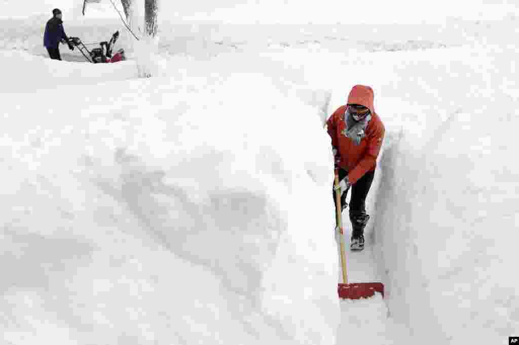 คิม เทยเลอร์ กำลังตักหิมะอยู่หน้าบ้านของเธอที่ Norwood รัฐแมสซาชูเซส พายุหิมะรอบนี้ นับเป็นรอบที่สี่ ภายในรอบหนึ่งเดือนที่พัดเอาความเหน็บหนาวเข้า New England และพื้นที่บริเวณชายฝั่งใกล้เคียง