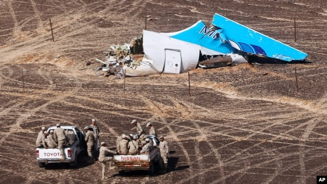 FILE - In this photo made available on Nov. 2, 2015, and provided by Russian Emergency Situations Ministry, Egyptian Military on cars approach a plane's tail at the wreckage of a passenger jet bound for St. Petersburg in Russia that crashed in Hassana, Egypt.