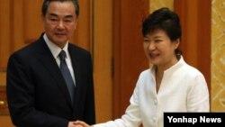 26일 청와대에서 박근혜 한국 대통령(오른쪽)이 왕이 중국 외교부장을 접견해 악수하고 있다.