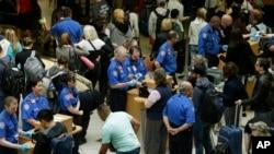 美国运输安全局工作人员在机场核对旅客的登机牌和身份。