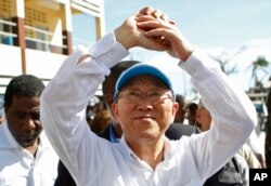 U.N. Secretary-General Ban Ki-moon makes a gesture of solidarity to people whose homes were destroyed by Hurricane Matthew, as he visits a school where they have sought shelter in Les Cayes, Haiti, Oct. 15, 2016.