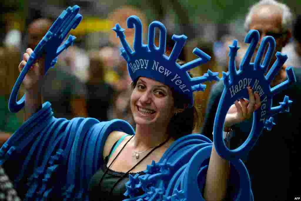 """Seorang perempuan menjual topi bertuliskan """"Happy New Year 2017"""" di jalanan Sydney, Australia."""