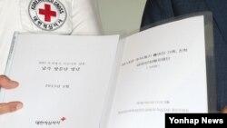 남북한이 이산가족 상봉 대상자 최종 명단을 교환한 지난 16일, 김성근 한국측 남북교류팀장(오른쪽)과 직원이 서울 대한적십자사에서 명단이 담긴 파일을 들어보이고 있다.