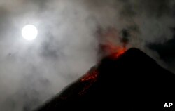 The super blue blood moon sets before dawn as lava cascades down the slopes of Mount Mayon volcano during a mild eruption as seen from Sto. Domingo township, Albay province around 340 kilometers (200 miles) southeast of Manila, Philippines, Feb. 1, 2018.