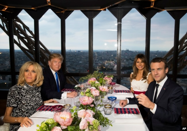 President Donald Trump, first lady Melania Trump, French President Emmanuel Macron his wife, Brigitte Macron, sit for dinner at the Jules Verne Restaurant on the Eiffel Tower in Paris, July 13, 2017.