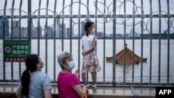 中國武漢居民注視著將要淹沒長江岸邊亭子頂部的洪水。 (2020年7月12日)