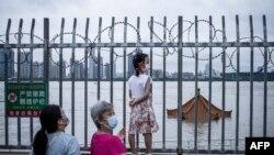 中国武汉居民注视着将要淹没长江岸边亭子顶部的洪水。(2020年7月12日)