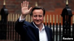 Britain's Prime Minister David Cameron waves as he leaves the Conservative Party headquarters in London, Britain, May 8, 2015.