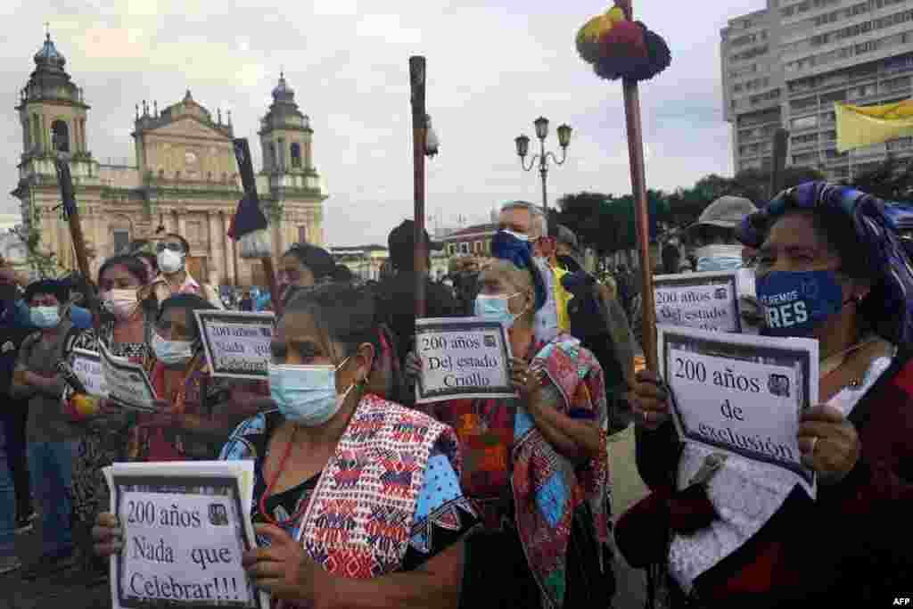 Los indígenas mayas sostienen carteles durante una protesta contra el Bicentenario de la Independencia de Guatemala.