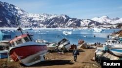 Seorang pria berjalan ke kapal miliknya melewati rongsokan kapal di Kota Tasiilaq, Greenland, 15 Juni 2018.