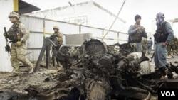Polisi Afghanistan (kanan) dan prajurit asing NATO menginspeksi lokasi serangan bunuh diri di Herat, Kamis (3/11).