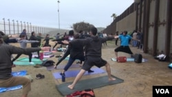 Yoga enthusiasts participate in a simultaneous session on both sides of the U.S.-Mexico border wall at Peace Park near San Diego, Calif., Feb. 11, 2017. (A. Martinez/VOA)