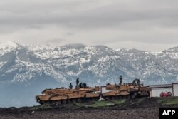 """FILE - Turkish tanks are parked near the Syrian border at Hassa, in Hatay province, Jan. 24, 2018, as part of the """"Operation Olive Branch."""""""