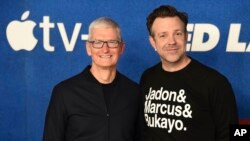 """Tim Cook, left, and Jason Sudeikis arrive at the premiere of the second season of """"Ted Lasso"""" on July 15, 2021, at the Pacific Design Center."""