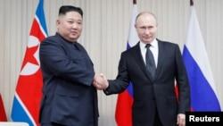 김정은 북한 국무위원장과 푸틴 러시아 대통령이 25일 블라디보스토크 루시크섬 극동연방대학에서 정상회담에 앞서 악수를 하고 있다.